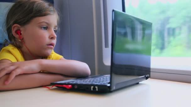 malá holčička hodinky na netbook, když sedí na vlak u okna