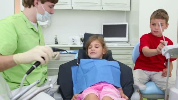 Zubař a chlapec dentální nástroje a dát do úst dívky
