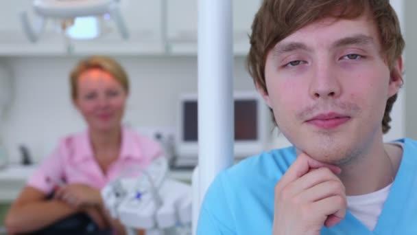 Krankenschwester lächelt Nahaufnahme und Arzt sitzt hinter unkonzentriert