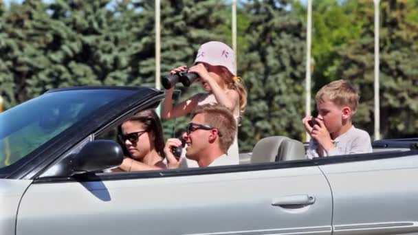 Students with kids sit in cabriolet girl looks through binocular
