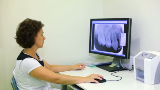 Doctor sits at work table and watches x-ray picture on display