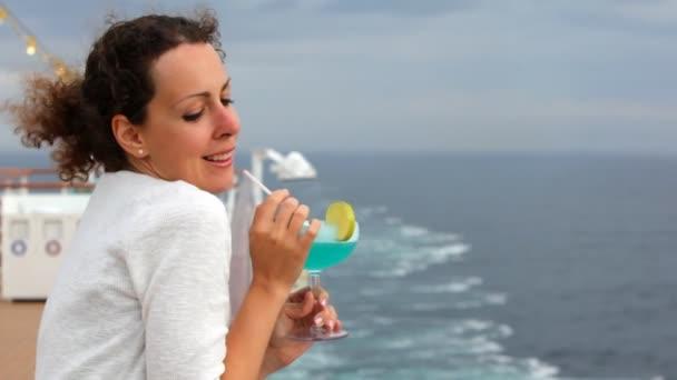 Žena s koktejlem v ruce stojí na palubě lodí a úsměvy