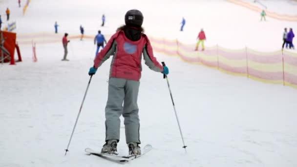 Frau in warmer Kleidung klettert auf Ski auf Schneehang