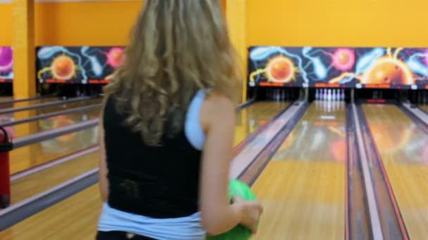 dívka hází bowlingovou kouli porazit kuželky a pak přejde velmi šťastný