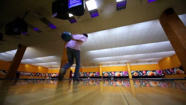 Člověk hodí bowlingovou kouli a dělá strike od beaty všechny kuželky