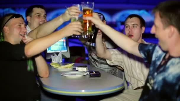 Pět přátel sedět a nápoje obsahují v tmavý klub