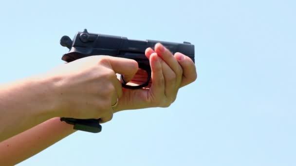 Nő tartja a pisztolyt és lő esküvői gyűrűs ujját