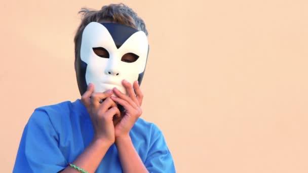 chlapec drží masky u tváře a pak odebere jeden pro druhého