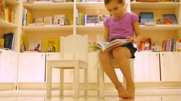 dvě malé holčičky, které sedí na židlích číst knihu v galerii dětí