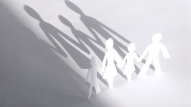 Figures of family cut from paper hold hands in sunlight