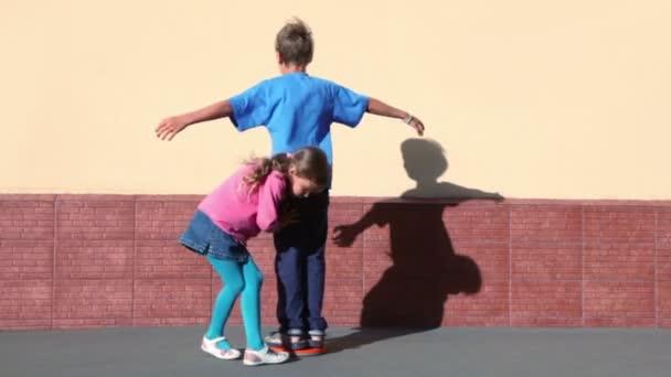 dívka otáčí chlapce, který točí s náručí umístěné blízko zdi