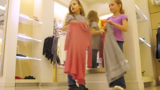 Girls Try On Clothes In Front Of Mirror In Shopping Center Stock