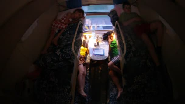 Family from four people is in dark compartment in train