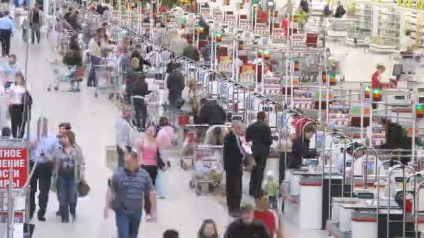 lidé nesou vozy s produkty do pokladny v supermarket