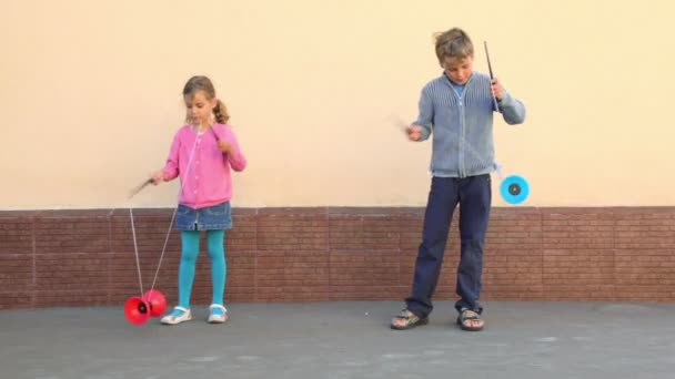 Two kids holds pairs of sticks and plays toy near wall