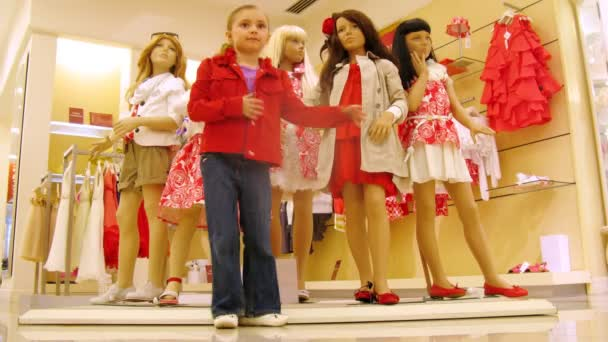 Girl stands near dummies in red dresses in shopping center