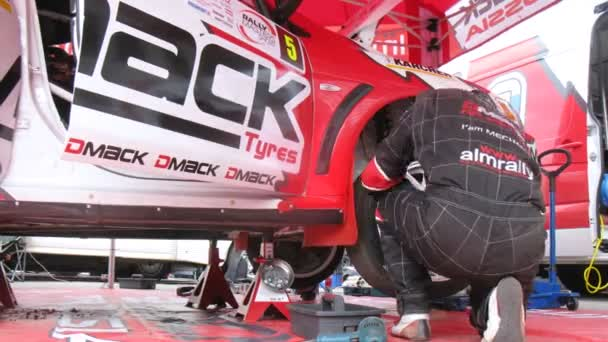Mechaniker baut Vorderrad am Auto des Teams alm russland auf
