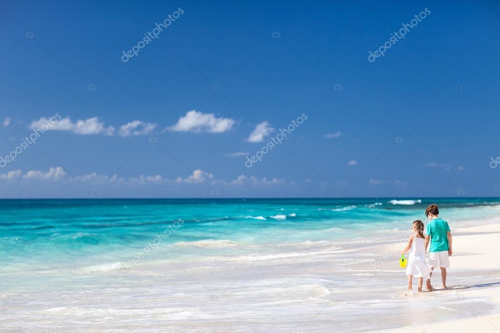 Two kids walking along a beach at Caribbean