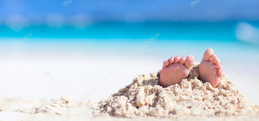 Little feet covered with sand