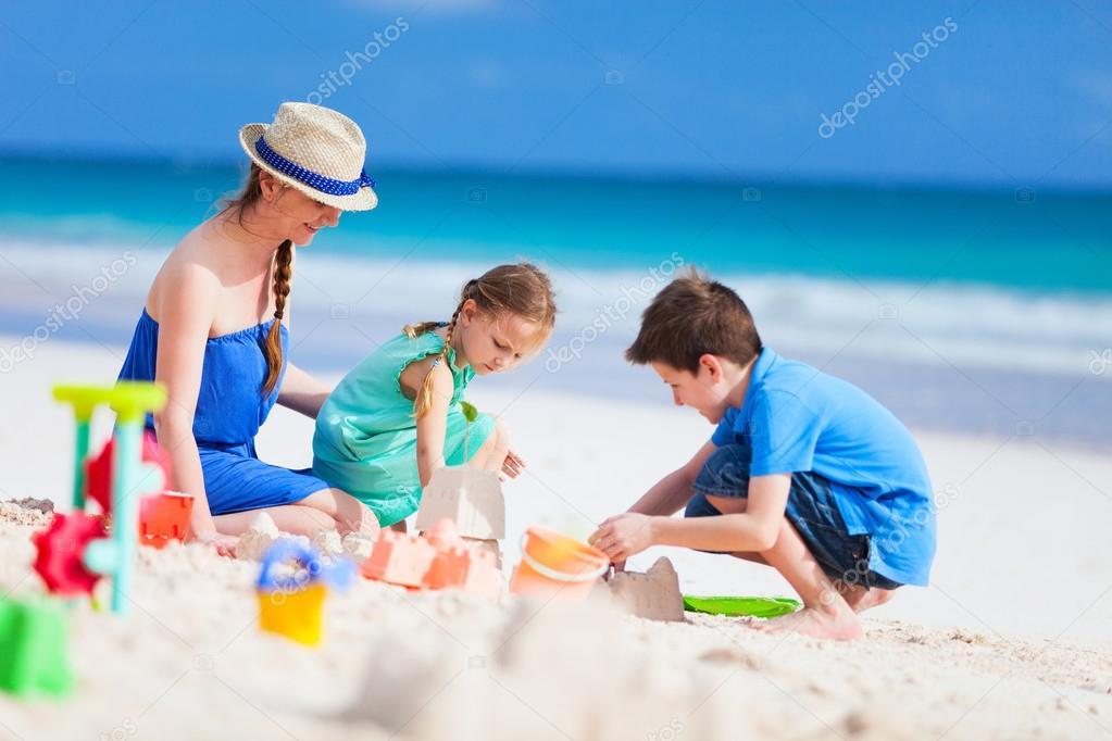 Madre Y Los Niños Jugando En La Playa