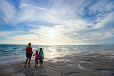 Mother and kids at beach silhouettes