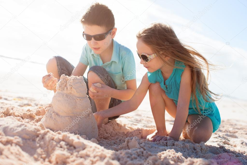 Two kids building sand castle