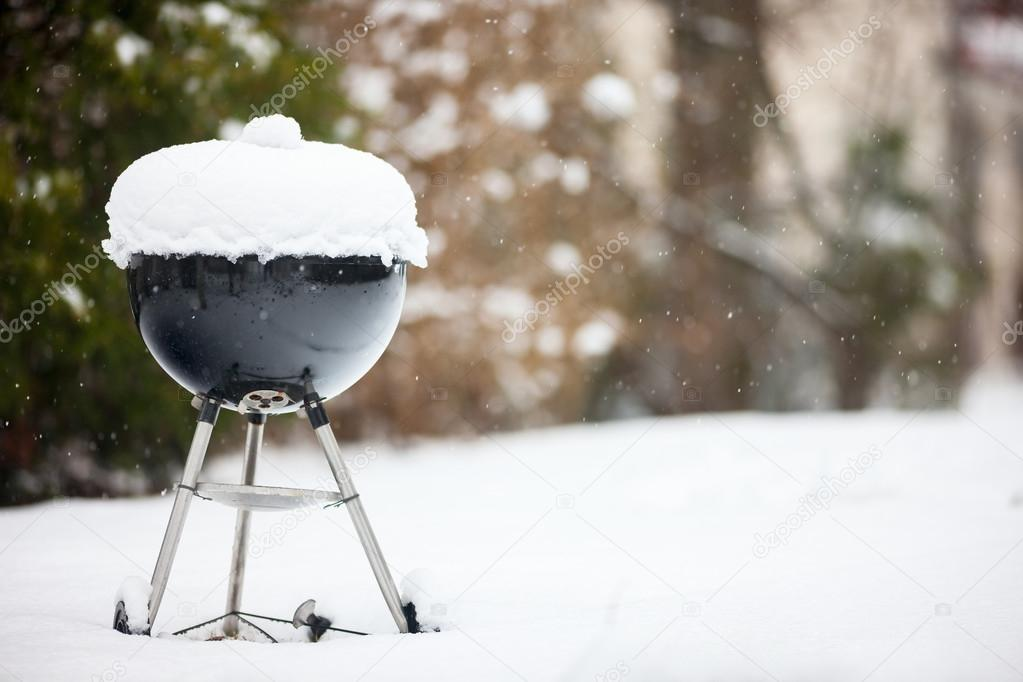 Barbeque grill covered with snow
