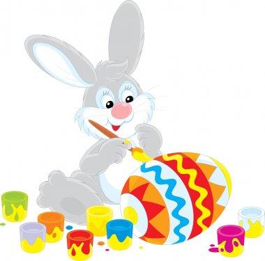 Easter Bunny decorating a big Easter egg