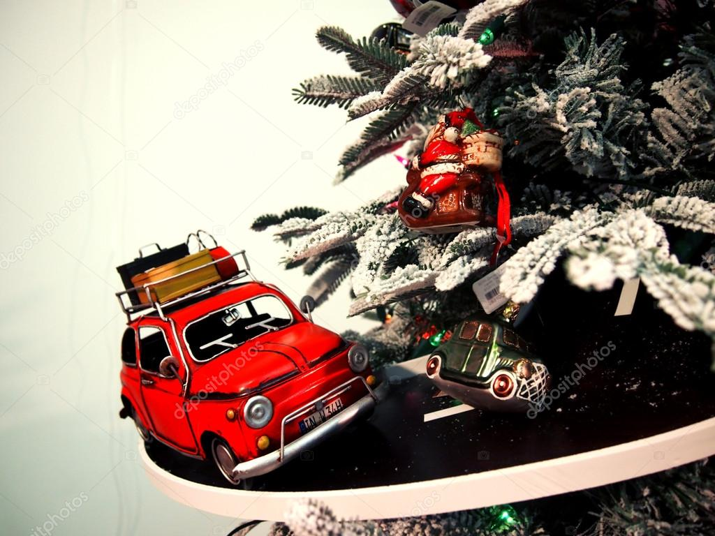 Toy car rides on the road around the Christmas tree