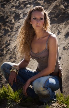Cowgirl in jeans on a sandy background