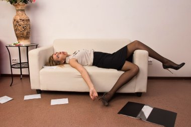 Lifeless business woman lying on sofa (imitation)