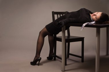 Woman in a black suit lying on a table