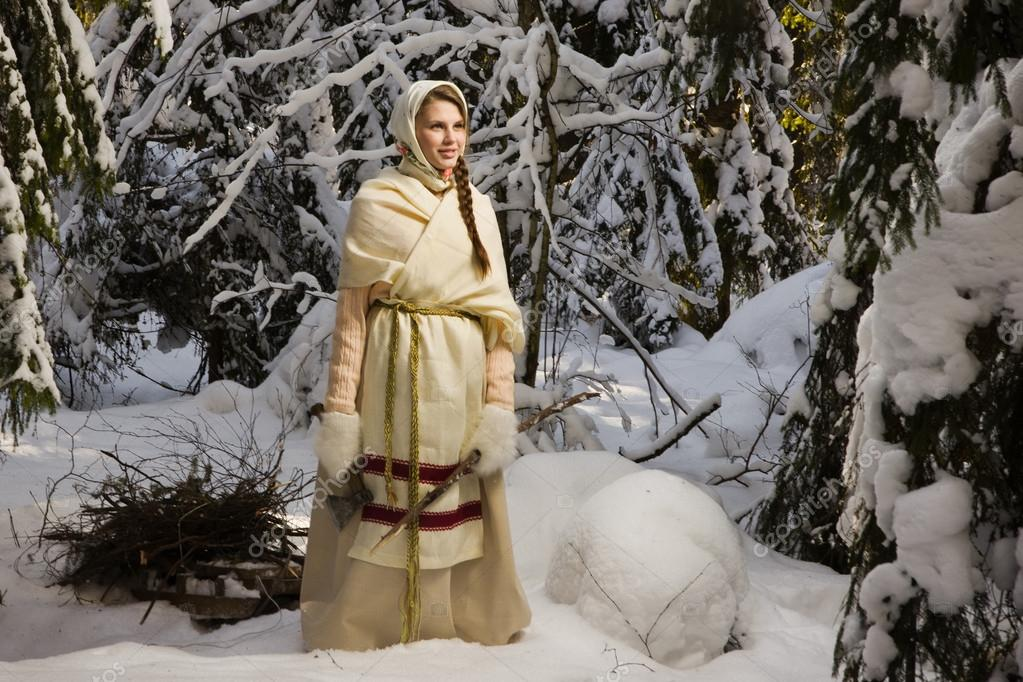 Russian girl with a sled in the winter woods