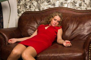 Crime scene simulation: lifeless blonde lying on the sofa