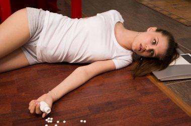 Crime scene simulation. Overdosed girl lying on the floor