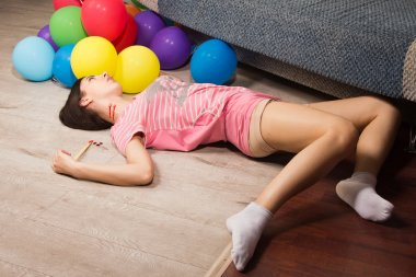 Lifeless woman lying on the floor (imitation)