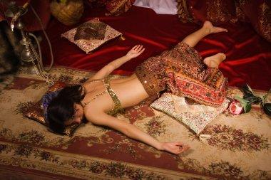 Crime scene imitation: lifeless woman in oriental costume lying
