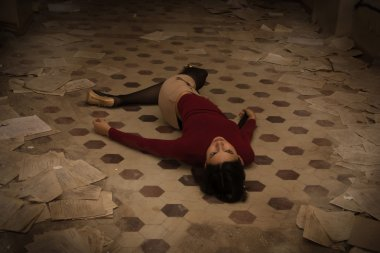 Lifeless brunette lying on the floor