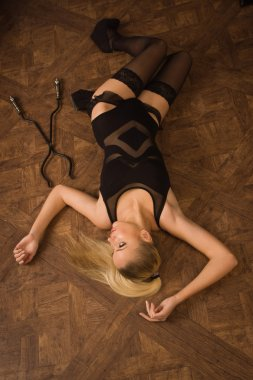 Lifeless woman in a luxurious lingerie lying on the floor