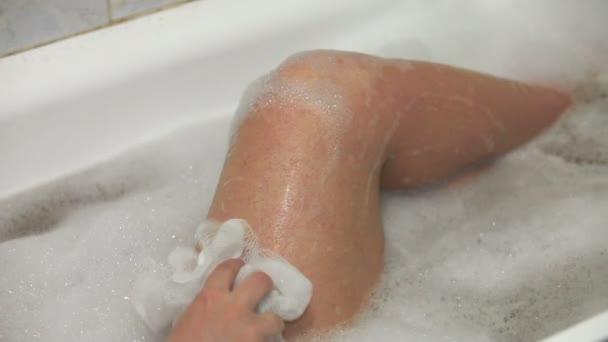 Woman in bath washing her leg with white sponge