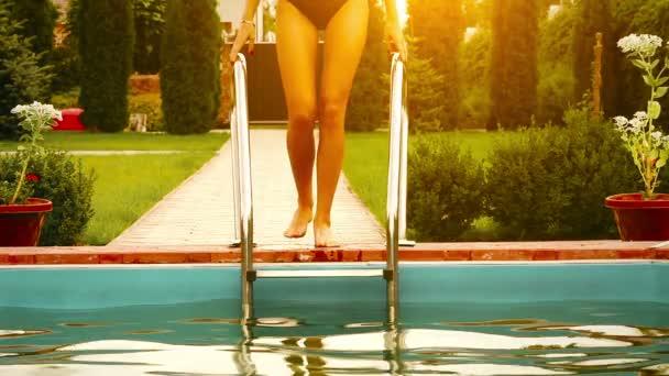 hezká dívka v bikinách v bazénu při západu slunce