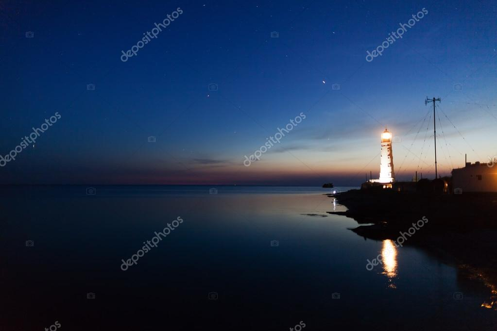 Lighthouse on the water edge at night