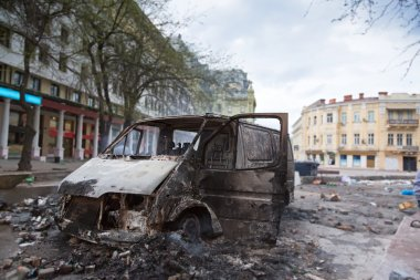 Burned car in the center of city after unrest