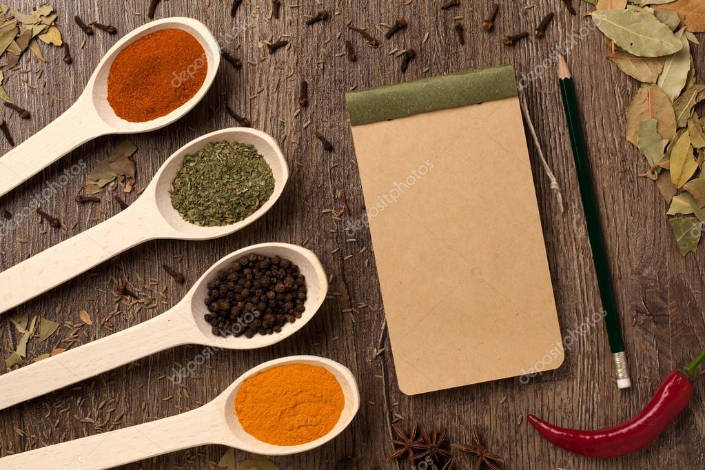 Peppers, spices in spoons, notebook and pencil