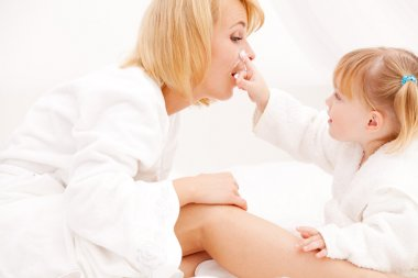 Mother and girl applying cream