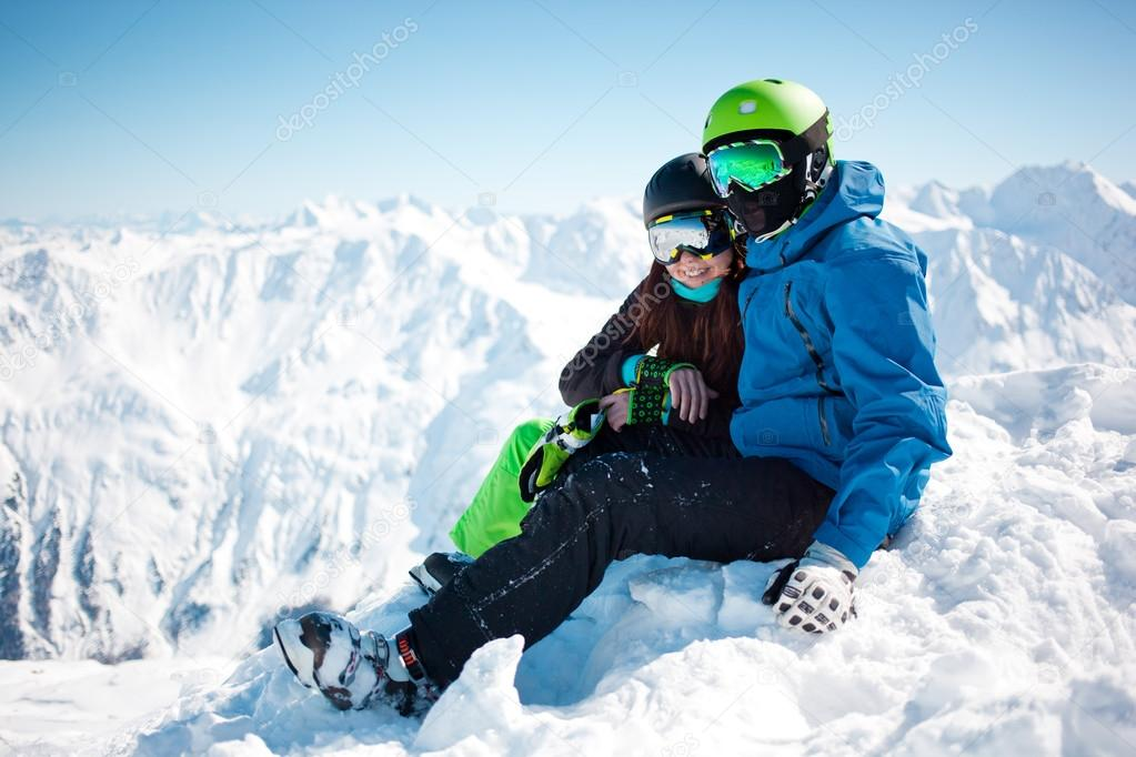 Young happy couple in snowy mountains.