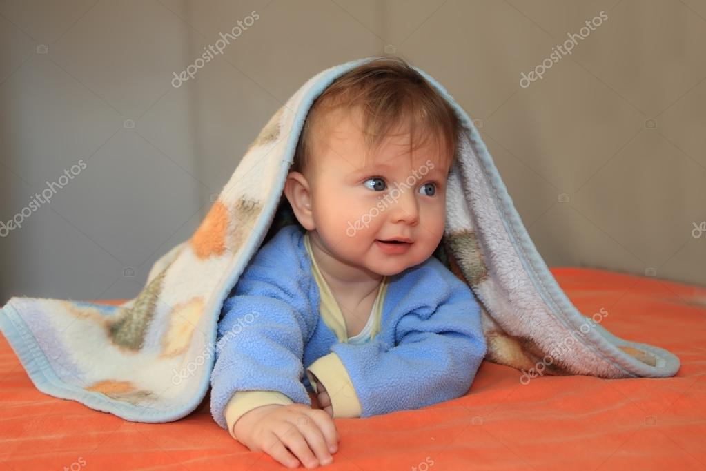 The blonde baby covered by a blanket