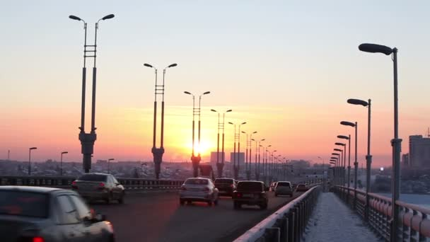 Cars driving on a bridge at sunset. Timelapse View