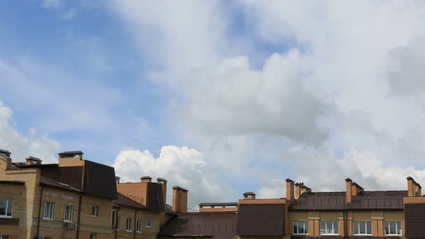 Cumulus clouds float above the apartment building. Timelapse View