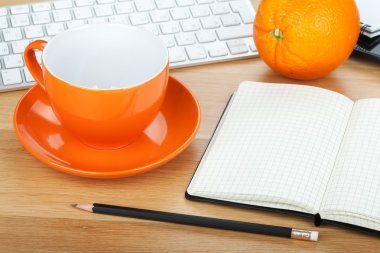 Coffee cup, orange fruit and office supplies
